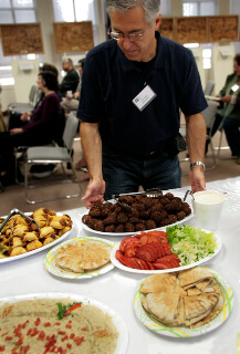 Anwar George Kenicer tries falafels and other Lebanese food from San Mateo's Tannourine restaurant at the August meeting. (photo © Jim Shubin)